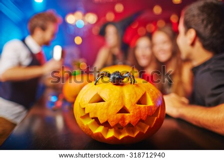 Carved pumpkin and spider on background of group of friends celebrating Halloween in bar - stock photo