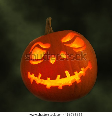 Carved pumpkin face for Halloween with smoky green background