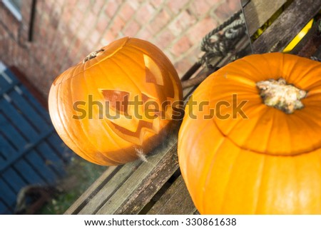 Carved pumpkin on a bench, looking into a mirror.   The reflection is in focus. - stock photo