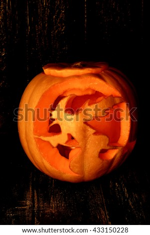 carved pumpkin with a witch on a black wooden background Halloween - stock photo
