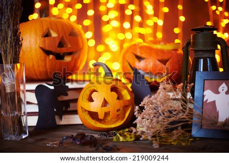 Carved pumpkins and other symbols of Halloween on sparkling background