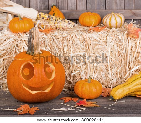 Carved smiling pumpkin and autumn squash and gourds