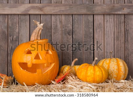 Carved smiling pumpkin and squash on a wood background - stock photo