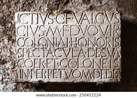 Carved stone panel in Latin at the ancient Roman city of Pompeii, which was destroyed and buried during the eruption of Mount Vesuvius in 79 AD. Italy Naples Pompeii - stock photo