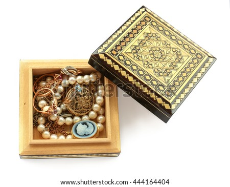 carved wooden box,  gold jewelry, ring with cubic zirconia, pendant, brooch, cameo, watches, pearl strand isolated