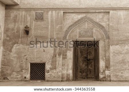Carved wooden door and  ornate plasterwork adorn a doorway in a courtyard of the restored traditional Arabian house of pearl trader Shaikh Isa bin Ali, Muharraq, Bahrain.