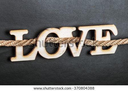 carved wooden letters love on a black background.It can be used for congratulations Mother Day and Valentine's Day - stock photo