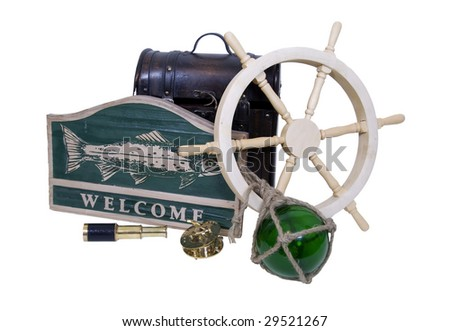 Carved wooden nautical sign with a large fish and the word welcome, ship steering wheel, glass float, old foot locker and brass instruments - Path included - stock photo