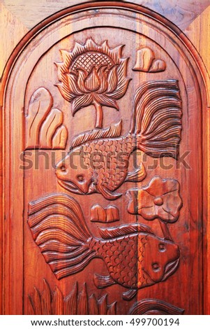 Carved wooden panel with fish on wooden door.