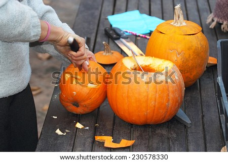 carving a fresh orange Halloween pumpkin - stock photo