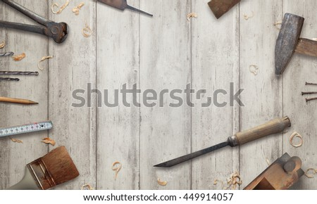 Carving with a chisel on wooden surface. Free space for text. Old tools beside.