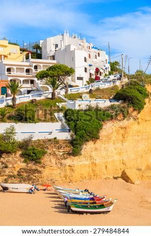 CARVOEIRO BEACH, PORTUGAL - MAY 17, 2015: typical fishing boats on beach in Carvoeiro coastal village. Carvoeiro is popular holiday tourist destination on Algarve coast. - stock photo
