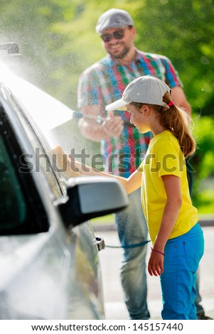 Carwash - young girl with father in carwash. - stock photo