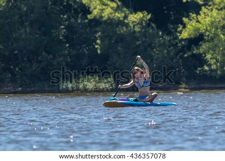 CARY, NORTH CAROLINA - JUN 12: Young lady enjoys paddle boarding on the lake on 12 Jun 2016 at Lake Jordan