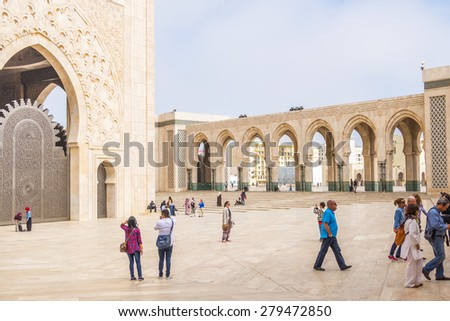 CASABLANCA, MOROCCO, APRIL 2, 2015: People gather on the outside grounds of Hassan II Mosque or Grande Mosquee Hassan II by misty morning - stock photo