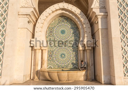 CASABLANCA, MOROCCO, DEC 25th 2014: Moroccan man sitting at the wall  in  the Great Hassan II Mosque. Casablanca, Morocco - stock photo