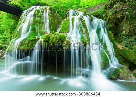 Cascade falls over mossy rocks in forest - stock photo