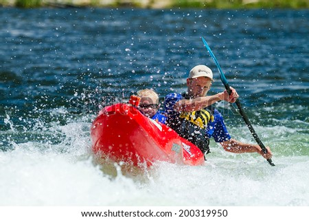 CASCADE, IDAHO/USA - JUNE 21, 2014: Father and son doing some canoe time during the Payette River Games - stock photo