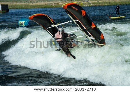 CASCADE, IDAHO/USA - JUNE 21, 2014: Rafter at the Payette River Games gets stuck in a wave and topples over.
