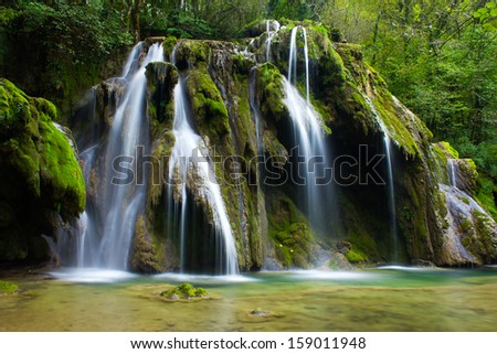 Cascade in picturesque setting - stock photo