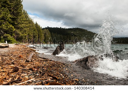 Cascade Lake wave splashes against two tree trunks at the lake edge