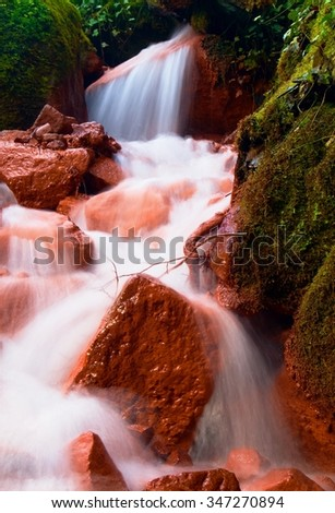 Cascades in rapid stream of mineral water. Red ferric sediments on big boulders between ferns - stock photo