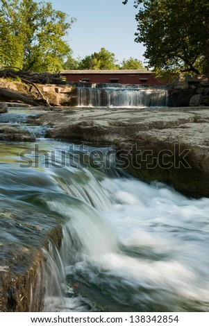 Cascading water downstream from red covered bridge - stock photo