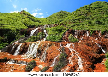Cascading water flowing down rock formations with lush green grass above it. - stock photo