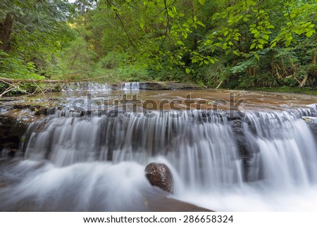 Cascading Waterfall Over Wide Ledge at Sweet Creek Falls Trail Complex in Mapleton Oregon - stock photo