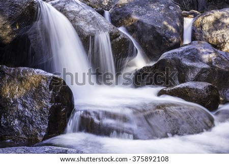 Cascading white water over red rock in Rocky Mountain stream - stock photo