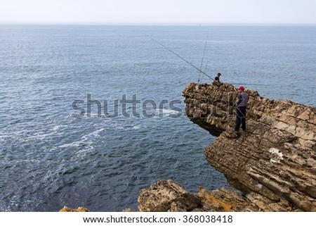 CASCAIS, PORTUGAL - SEPTEMBER 29, 2015: Men fishing along the rugged coast of Cascais, on September 29, 2015, in Cascais, Portugal - stock photo