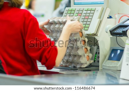 Cash-desk with cashier and terminal in supermarket. Serve customer - stock photo