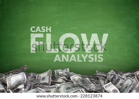 Cash flow analysis on green blackboard with dollar bills - stock photo