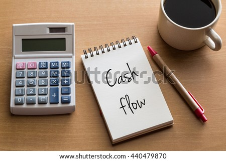 Cash flow business/finance conceptual - handwriting on notepad with cup of coffee and calculator - stock photo