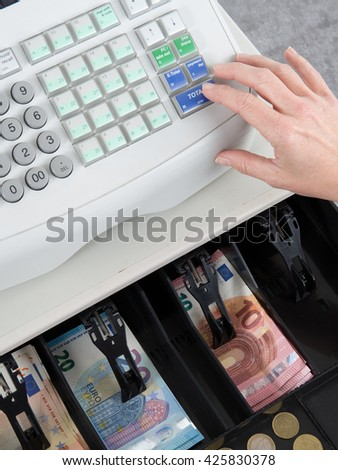 Cash Register and finger on the machine - stock photo