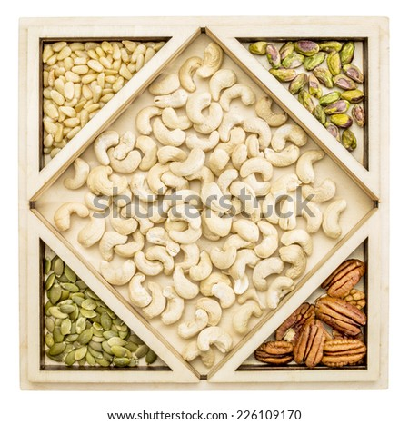 cashew and other nuts (pecan,  almond, pine, pistachio, peanut) in a geometrical wood tray - stock photo