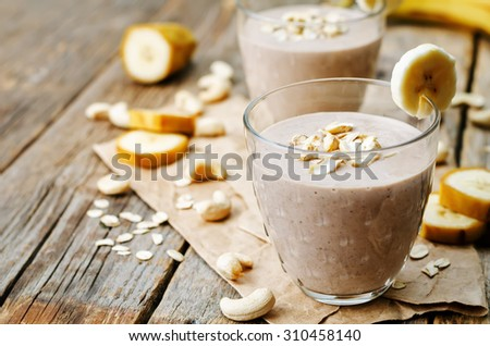 cashew banana cocoa oats smoothie on a dark wood background. the toning. selective focus - stock photo