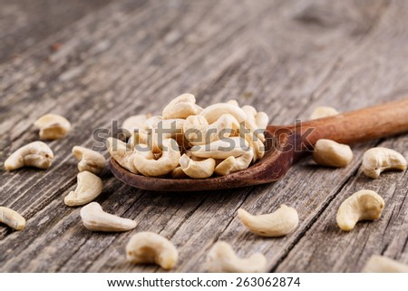 Cashew nuts on a wooden spoon. - stock photo