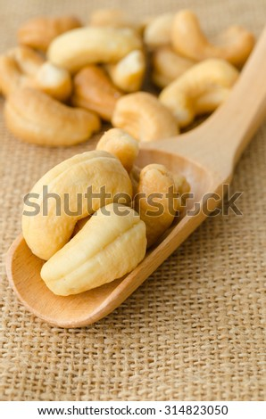 cashew nuts with salt and wooden spoon on sack background. - stock photo