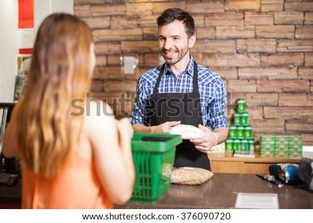 Cashier and customer smiling face to face while buying groceries at a supermarket - stock photo