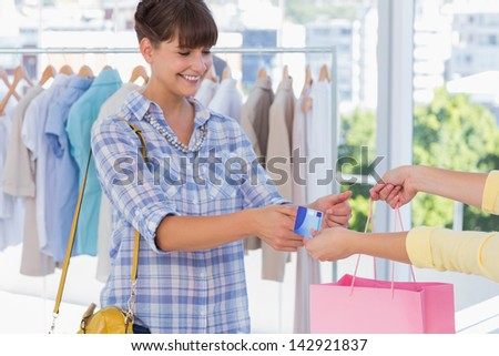 Cashier giving credit card and shopping bag to a smiling customer
