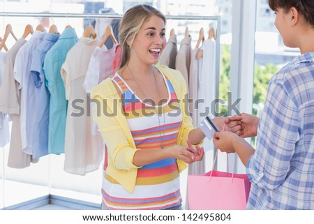 Cashier giving credit card to customer in a bright shop - stock photo