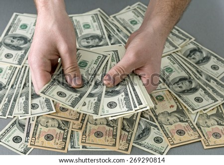Cashier hands. Man holding larges stack of US cash notes above desk covered with layer of dollars notes of different value - stock photo