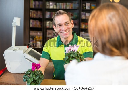 Cashier or shopkeeper in flower shop or retail store serving a customer