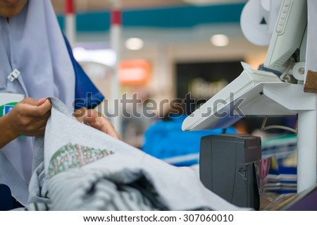 Cashier serves customer at cash desk with computer terminal in supermarket - stock photo