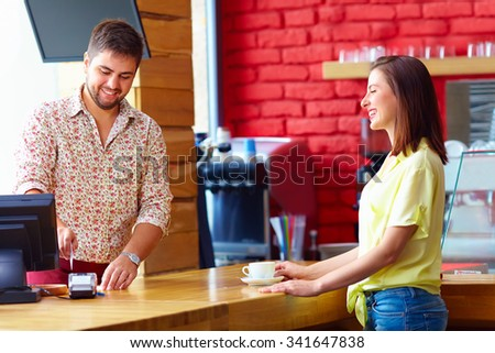 cashier serves customer at the cash desk in cafe