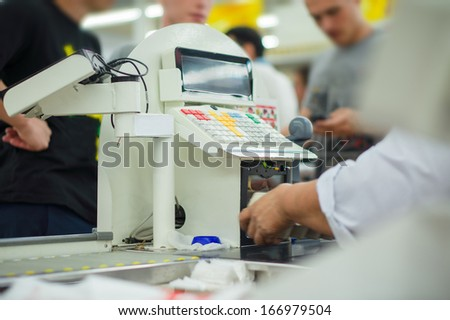 Cashier serves customers  at cash desk in supermarket - stock photo