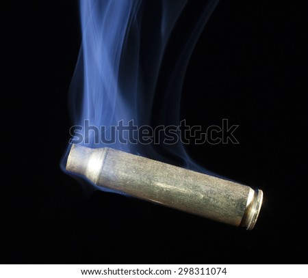 Casing from a rifle cartridge that has been shot and is smoking - stock photo