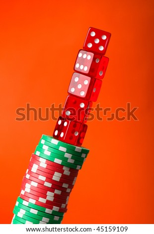 Casino chips and cards against red background - stock photo