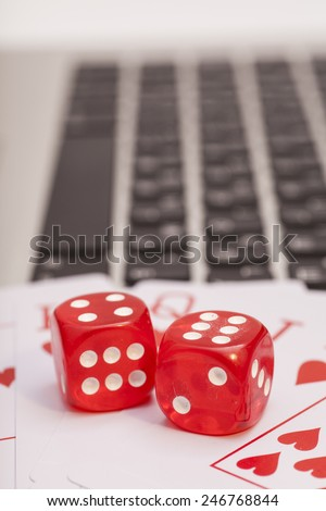 Casino chips, cards and dices stacking on laptop - stock photo